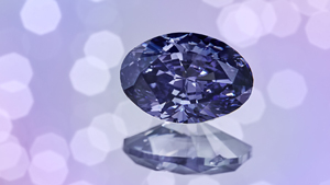 An oval shaped purple diamond on a pink, green, blue and white background.