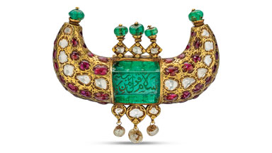 This Mughal era gold horn pendant features a 125 carat Colombian emerald engraved in Arabic. It is set with diamonds, Burmese rubies, emerald beads and pearls.