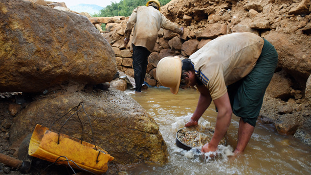 Burmese miner washes samples collected from gravel