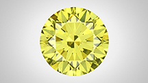Face-up view of a green-yellow round brilliant diamond.