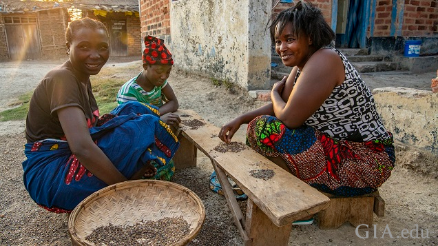 Three woman sit on the ground around a low bench/table to sort through gravel for gems.