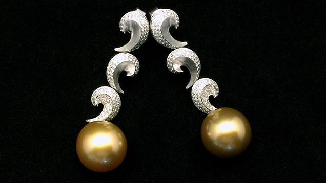 A pair of pearl and diamond earrings set with one CVD synthetic melee.