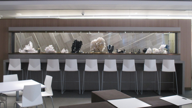 A view of the dramatic long, narrow exhibit case filled with GIA Museum pieces. The case is a feature wall in the student commons area filled with tables and chairs.
