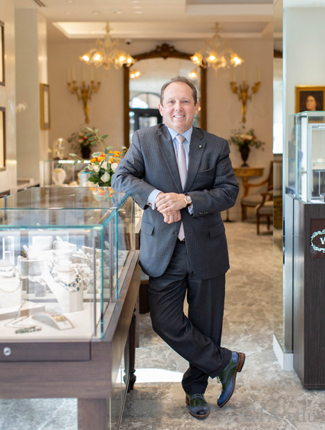Standing man in a suit leans on a jewelry counter.