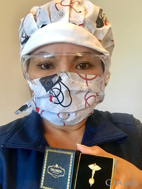 A nurse in googles and a mask holds a box with the Defeating the Coronavirus pin in it.