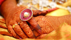 A spaceship-inspired ring of pink gems surrounding a pearl is showcased on a bride's intricately drawn henna hands.