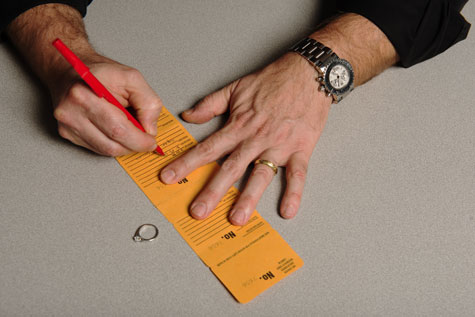 Close-up of jeweler writing customer sizing information on job envelope