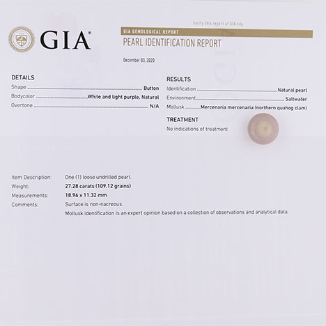 A quahog pearl sitting on a printed GIA Pearl Identification Report.