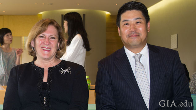 Susan Jacques and Ken Fujita, dressed in business attire, sit side-by-side at an event.