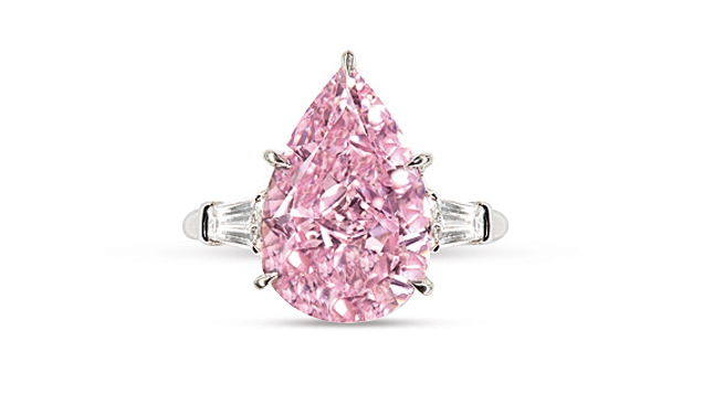 The pear shaped pink diamond is set in a ring and flanked by two colorless baguettes.