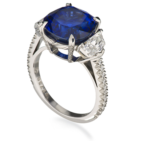 Perspective view of a platinum ring, featuring a sapphire centre stone flanked by diamonds and with diamonds set in the shank