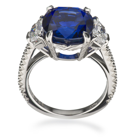 Side view of a platinum ring, featuring a sapphire centre stone flanked by diamonds and with diamonds set in the shank