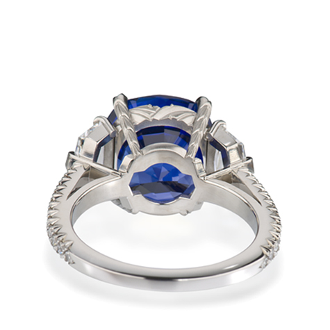 View of the underside of a platinum ring, featuring a sapphire centre stone flanked by diamonds and with diamonds set in the shank