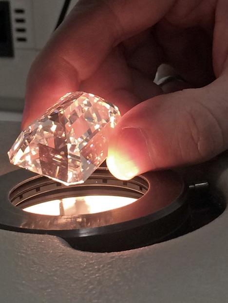 在强烈的光照下手握一颗超级大钻石。