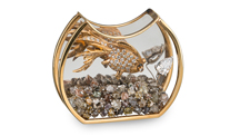 A crescent-shaped bowl with a flat bottom trimmed in gold holds rough diamond gravel and a gold and diamond fish.