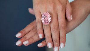 The 59.60 ct mixed-cut oval CTF Pink star diamond is displayed on a woman's hands.  It is wider than her ring finger.