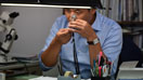Dr. Ken Fujita uses a loupe to examine a gemstone at his desk.