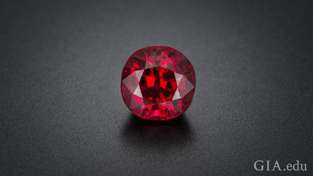 A round, bright red gem displayed on a dark gray background.