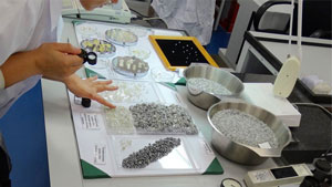 A sorter works at a table lined with sorted piles of diamond rough.