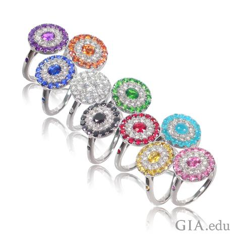 A group of circular-shaped rings 11 rings. Rings have rubies; blue, pink, yellow and orange sapphires; tsavorite garnets; amethysts; or Paraíba tourmalines – and diamonds.