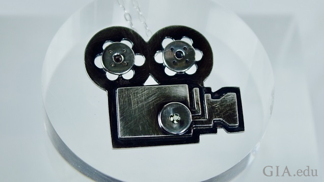 A black sterling silver pendant of a movie camera and film reels.