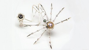 The body and legs of the spider palm bracelet rests on top of the hand; the egg and web nest are the ring.