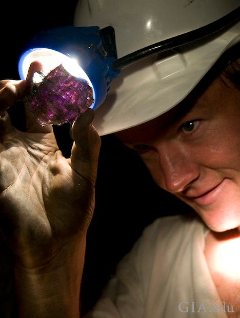Man holds up a piece of Tanzanite and shines his headlamp on it.