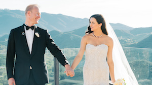 Wedding couple: Groom in black tuxedo and woman in white gown hold hands and gaze at one another. California hills in the background.
