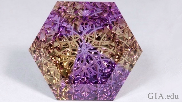 An octagonal shaped, intricately carved ametrine (citrine and amethyst).