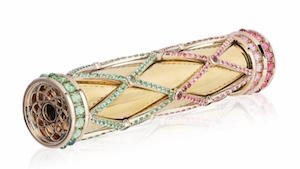 Lattice-patterned gems encase an 18K gold kaleidoscope.