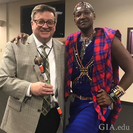 A man in a suit with a man in Masai tribal clothes pose together.