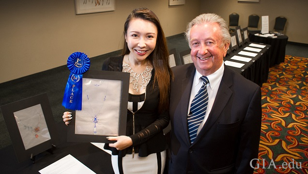 Woman holds a rendering with a blue ribbon with a man standing next to her.