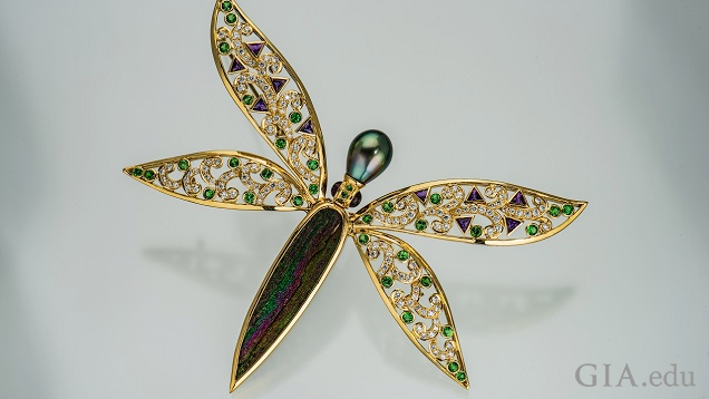 Dragon fly pin with drusy body and pearl head; wings are set with clear and green gems.