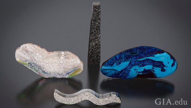 Organically shaped pieced of agate drusy with a variety of coatings. One with a silicone dioxide coating, one with a black titanium coating, one with a blue titanium coating and one with a platinum coating.
