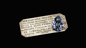A large pear shaped diamond sits on a silver plaque with French words.