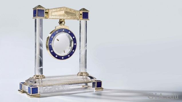 Base and frame of the clock are clear rock crystal and blue and gold material. The clock face, also clear rock crystal with blue and gold material, hangs from the upper frame.