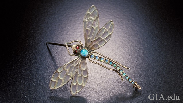 View of a dragonfly brooch from above. Translucent wings and body of blueish opal.
