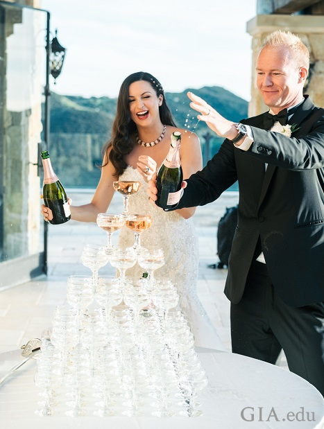 Wedding couple pours champagne over a tower of champagne glasses.