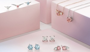 Clear, blue and pink synthetic diamond jewelry is displayed around and on pink boxes.