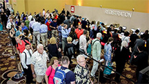 Show attendees at registration booths.