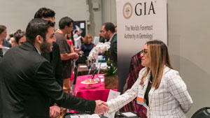 A man and woman shake hands during a career fair event. In the background is a GIA poster.
