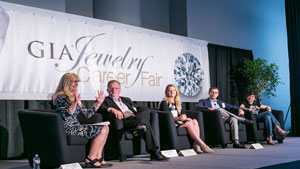 Four industry panelist and one moderator are seen sitting on stage while giving career advice.