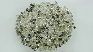 A pile of rough diamonds of various colors.