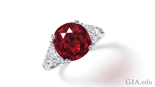 A round ruby is flanked by diamonds in a ring.