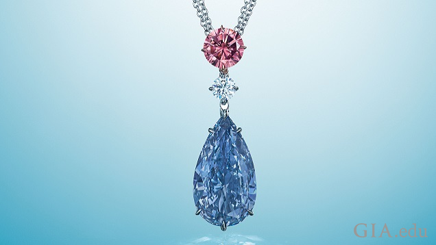 A large blue pear-shaped diamond hangs from a colourless and pink diamond.