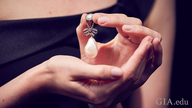 A large pearl hangs from a diamond pendant.