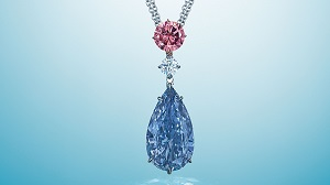 A large blue pear shaped diamond hangs from a colorless and pink diamond.