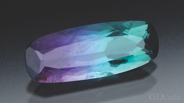 An elongated rectangular cut tourmaline displays shades of purple and tourquoise.