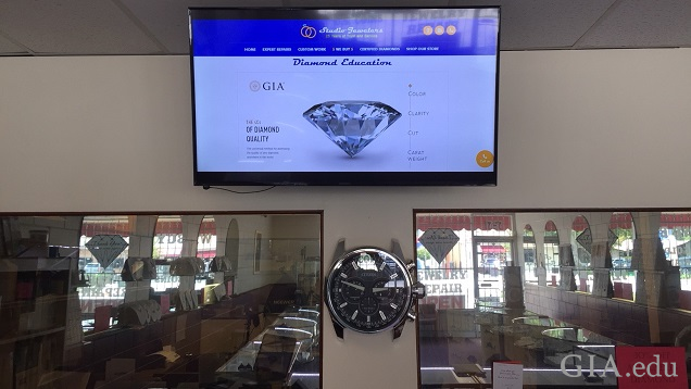 A large TV hangs in a jewelry store.