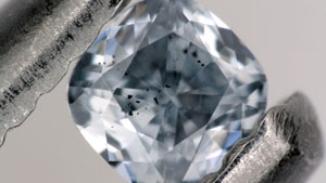 A blue diamond with inclusions under the table is held up in tweezers.
